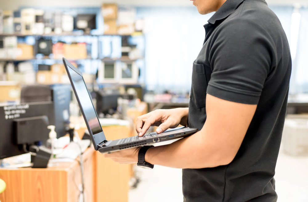 IT-support-technician-stands-holding-a-laptop-in-an-open-office-space